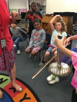 Elementary student bows a waterphone in front of classmates.