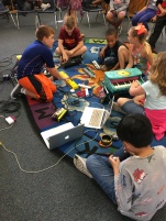 Students working together to create a cohesive improvised piece using electronics and toy piano.