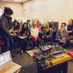 An excited university student, demonstrates how the body can be a synthesizer with the use of a Source Audio Hot Hand Wireless MIDI Controller to fellow classmates.